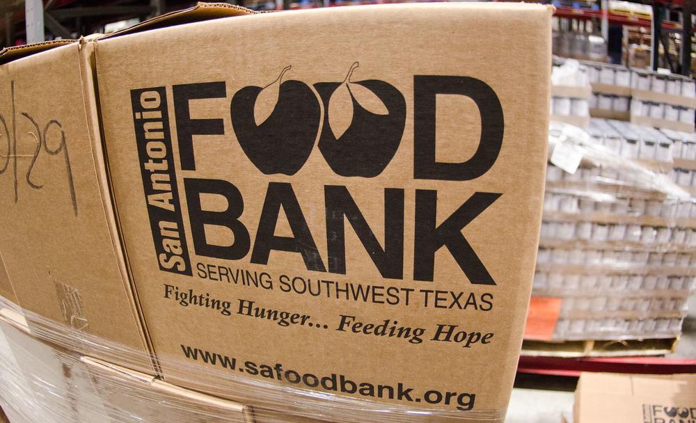 """Paket im Vordergrung, auf dem steht """"Foodbank, Fighting Hunger ... Feeding Hope""""."""