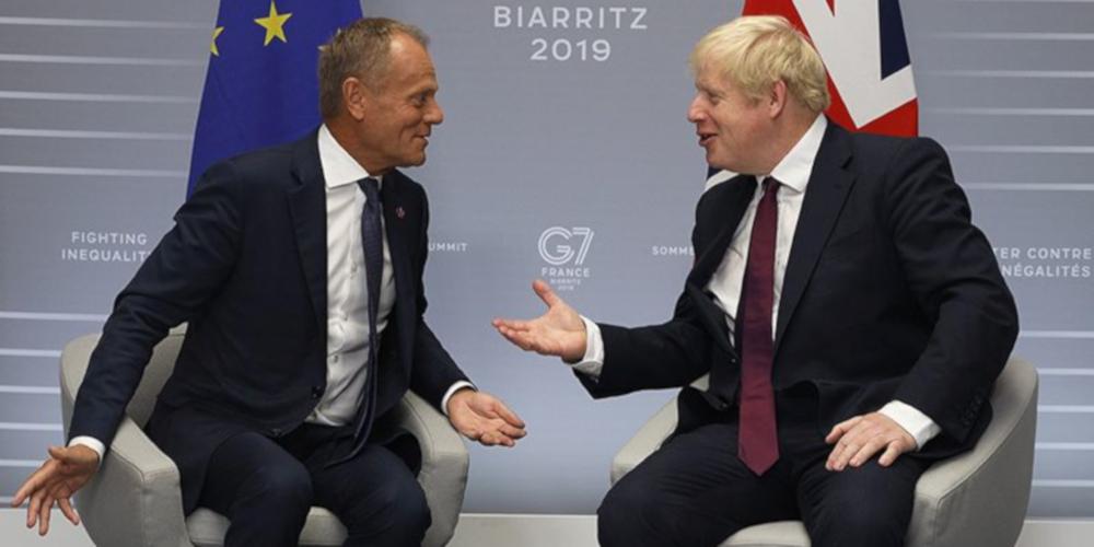Boris Johnson spricht mit Donald Tusk beim G7-Gipfel. Beide sitzen nebeneinander in kleinen grauen Sesseln und gestikulieren.