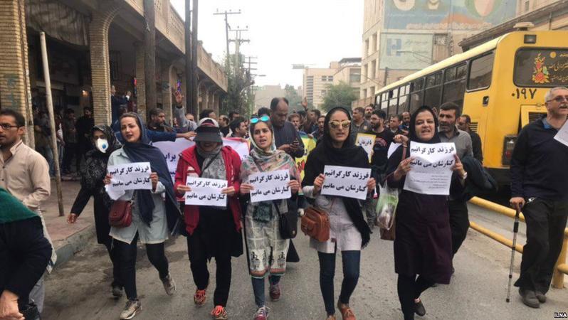 Frauen marschieren mit handgemalten Zetteln in den Händen in der ersten Reihe bei einer Demonstration in Iran.