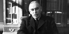 John Maynard Keynes am Schreibtisch mit einem Buch in der Hand. Bild in Schwarzweiß.
