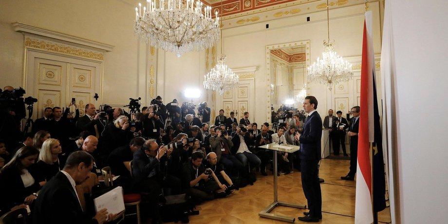 Rechts steht vor einer österreichischen Flagge, von der Seite zu sehen, Sebastian Kurz und spricht bei einer Pressekonferenz zu Journalisten. Der Raum ist prächtig mit Kronleuchter, im Kanzleramt in Wien.