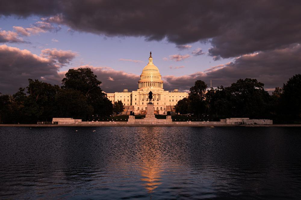 Das Kongressgebäude mit seiner berühmten Kuppel ist jenseits eines Gewässers zu sehen. Am Himmel hängen düstere Wolken.