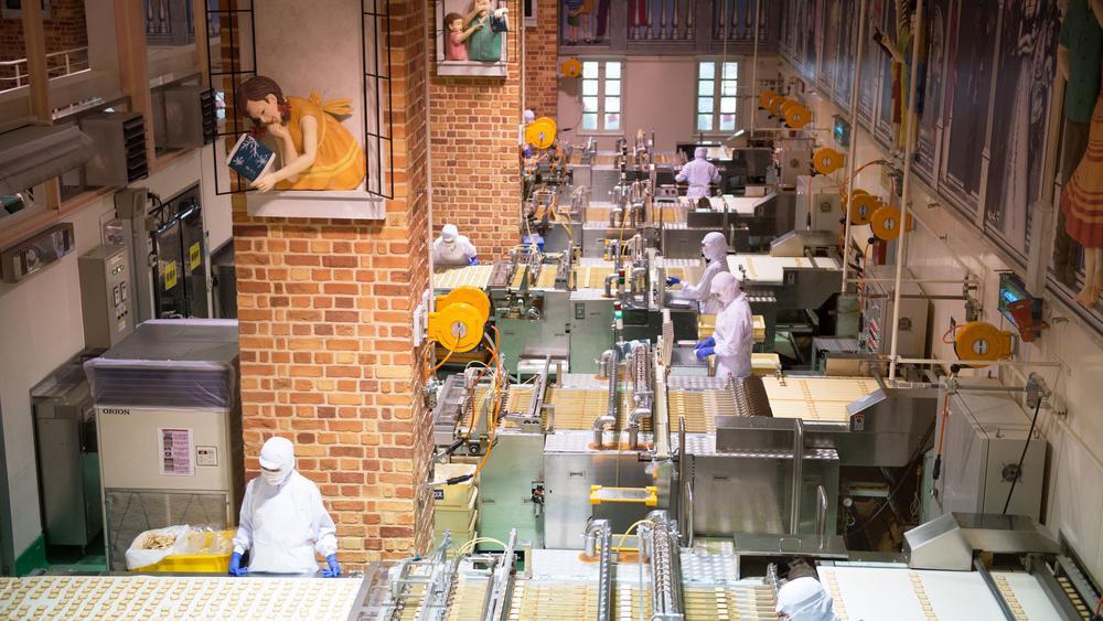 Schokoladenfabrik in Tokyo, Blick von oben auf Arbeiter an Produktionsbändern.