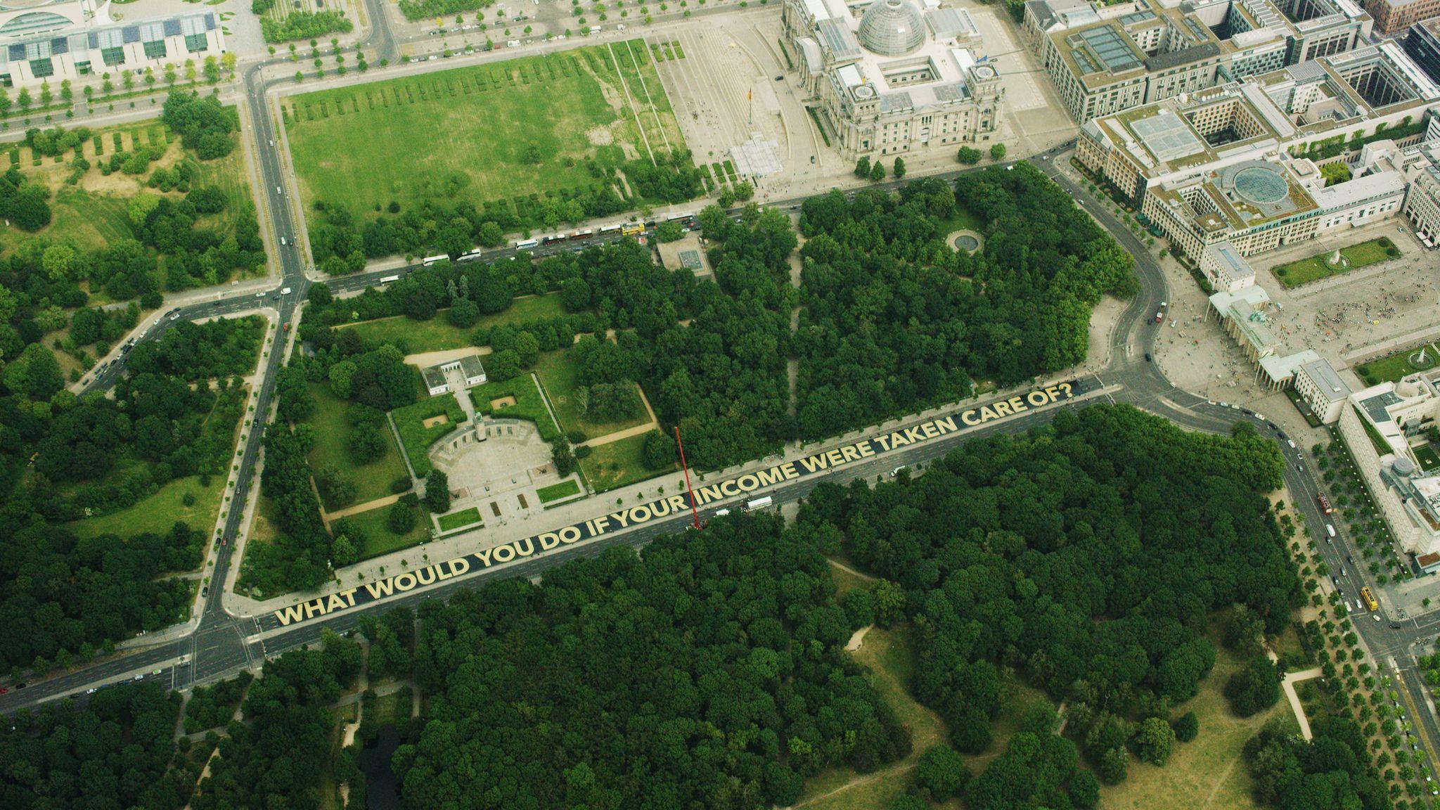 Luftaufnahme  von der Straße des 17 Juni, auf der in Großbuchstaben der ausgelegt ist: What would you do if your income is taken care of?