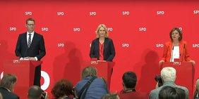 Thorsten Schäfer-Gümbel, Manuela Schwesig und Malu Dreyer stehen an roten Pulten bei einer Pressekonferenz