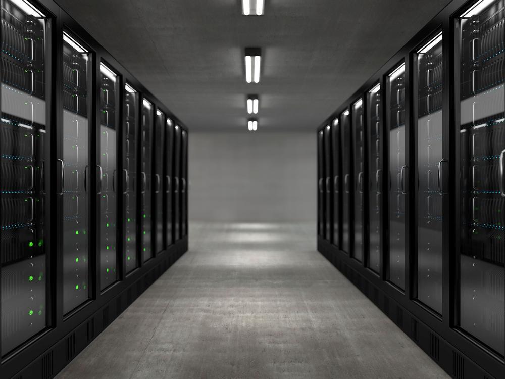 Blick in einen Gang mit großen Servern rechts und links. Schwarzweißbild.