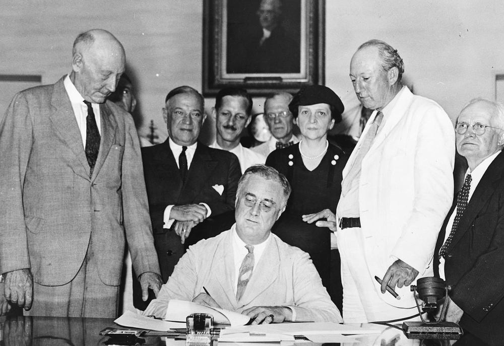 Schwarzweiß-Bild von Franklin D. Roosevelt an einem Schreibtisch, der ein Dokument unterzeichnet. Er ist von mehreren Männern umgeben.