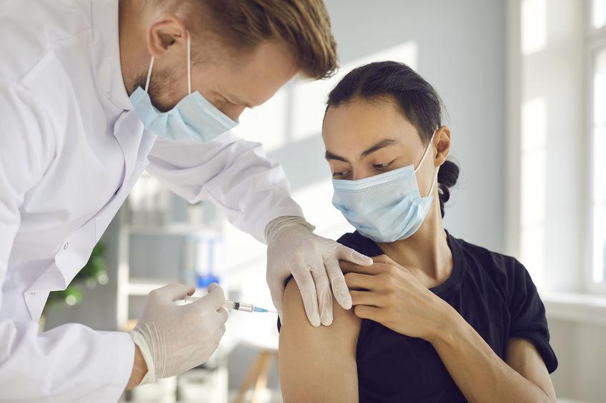 Ein Arzt mit medizinischer Maske impft eine Frau im T-Shirt, die ebenfalls einen Mund-Nasen-Schutz trägt.
