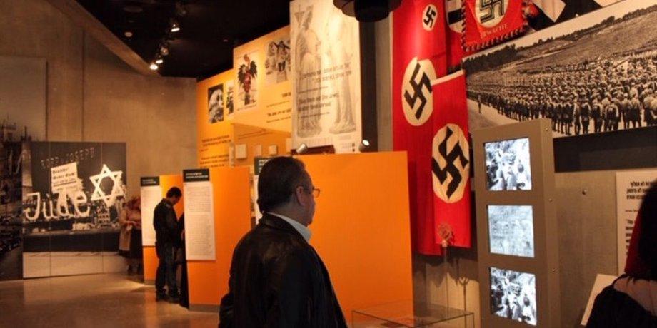 """Blick in die Ausstellung in Yad Yashem. Auf der linken sind rote NS-Flaggen mit Hakenkreuzen auf weißem Grund im Zentrum, auf der hinteren Wand ist ein Bild mit einem Geschäft zu sehen, dessen Schaufenster mit """"Jude"""" beschmiert ist."""