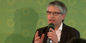Der grüne Spitzenkandidat bei der Europa-Wahl Sven Giegold spricht mit Mikrofon in der Hand.