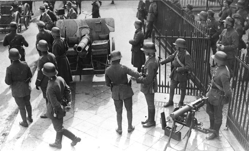 Schwarzweißbild von Soldaten mit einer Kanone auf einer Berliner Straße.