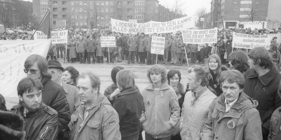 Schwarzweißbild mit Streikenden mit Parkern und Mänteln, die Transparente und Plakate in die Höhe halten.