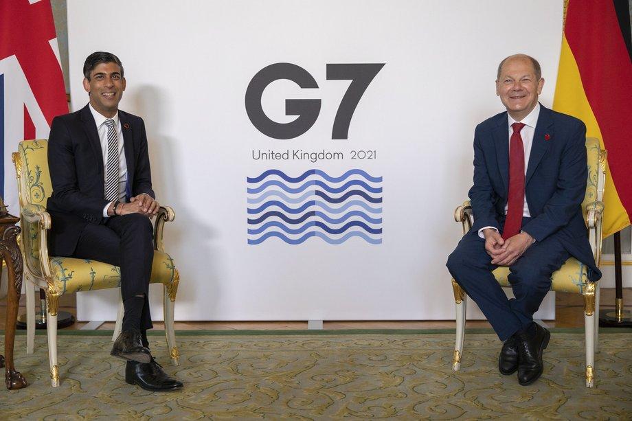 Der englische Finanzminister sitzt links, rechte mit etwa 1,50 Meter Abstand der deutsche, jeder vor der Flagge seines Landes. Auf der Wand zwischen ihnen steht G7, United Kingdom 2021.