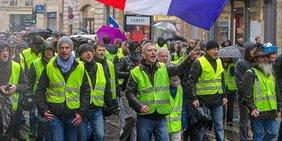 Protest der Gelbwesten in Frankreich, im Vordergrund ein Mann mit einer französischen Fahne.