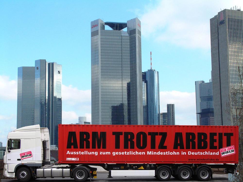Ein Lkw mit einem roten Container, auf dem steht: Arm trotz Arbeit.