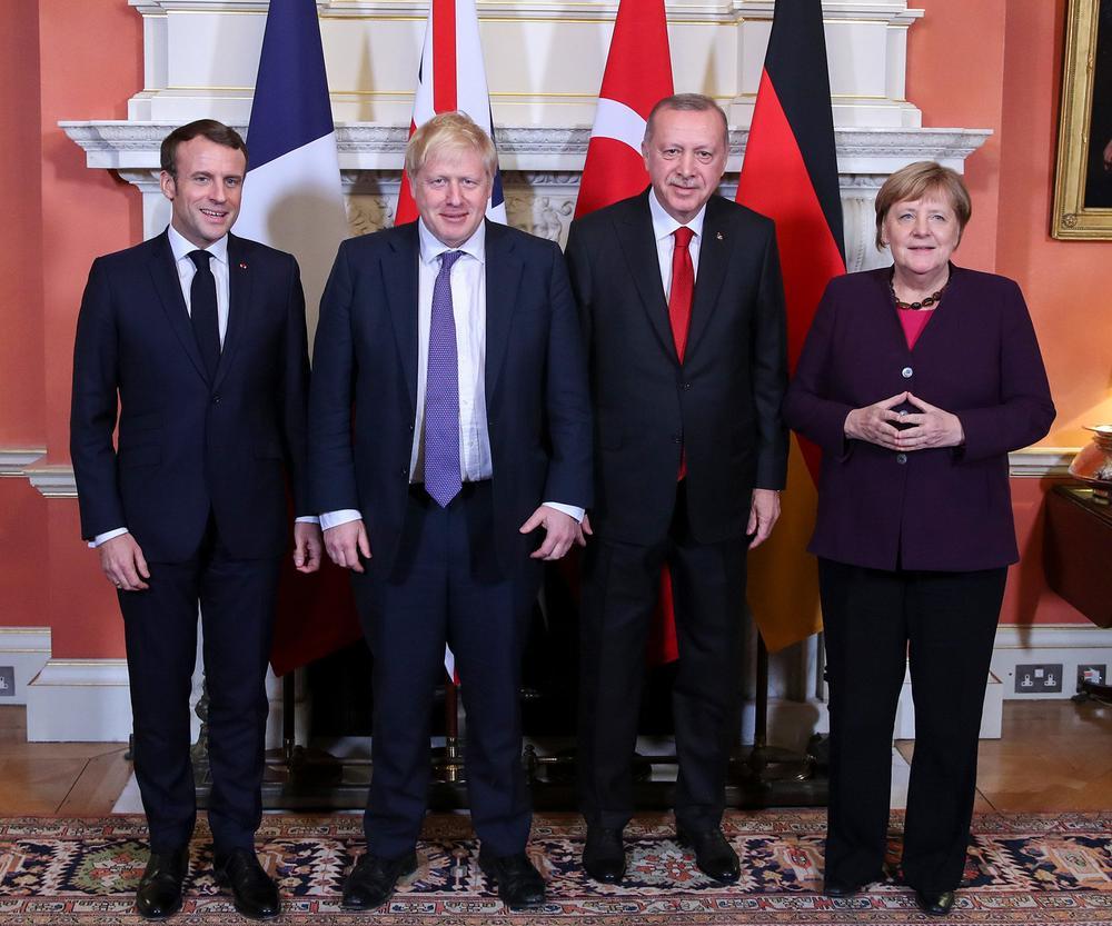 Emmanuel Macron, Boris Johnson, Tayyip Erdogan und Angela Merkel stehen nebeneinander vor ihren jeweiligen Landesflaggen.