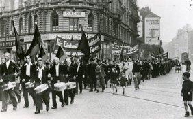 Schwarzweißbild von einem Maiumzug, im Vordergrund Trommler, dahinter Fahnenträger. Transparente fordern die Einheit Deutschlands und einen gerechten Frieden.