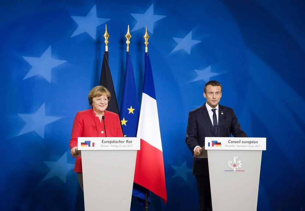 Angela Merkel und Emmanuel Macron stehen hinter Rednerpulten vor einer blauben Wand mit Sternsymbolen im Kreis und Flaggen von Deutschland, Frankreich und der EU.