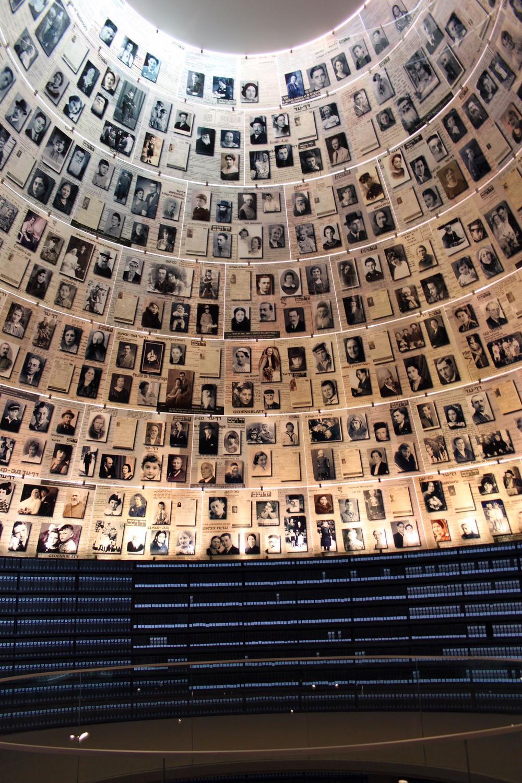 In einem hohen zylindrisch geformten Raum hängen dicht an dicht Fotos von Opfern der Schoah.