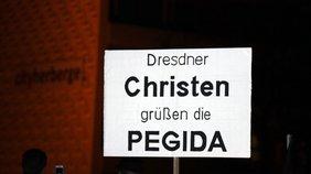 """Ein Schild mit der Aufschrift """"Dresdener Christen begrüßen Pegida"""" wird hochgehalten. Von dem Arm ist nur der Teil bis zum Ellbogen zu sehen."""