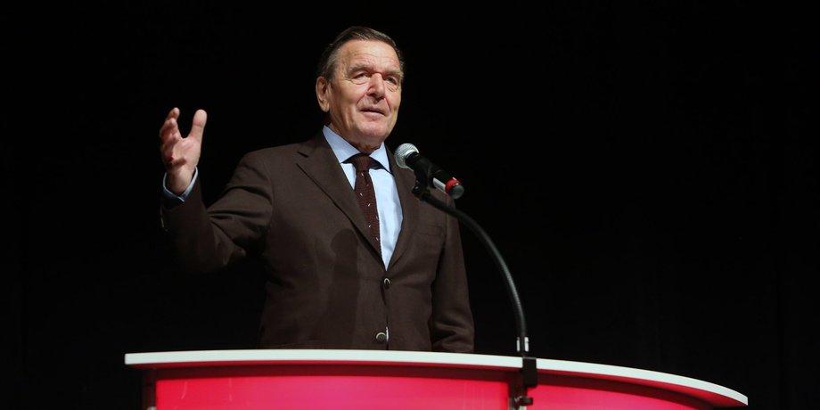 Gerhard Schröder hält eine Rede im Jahr 2013. Er trägt einen brauen Anzug und steht hinter einem runden roten Pult, auf dem SPD steht.