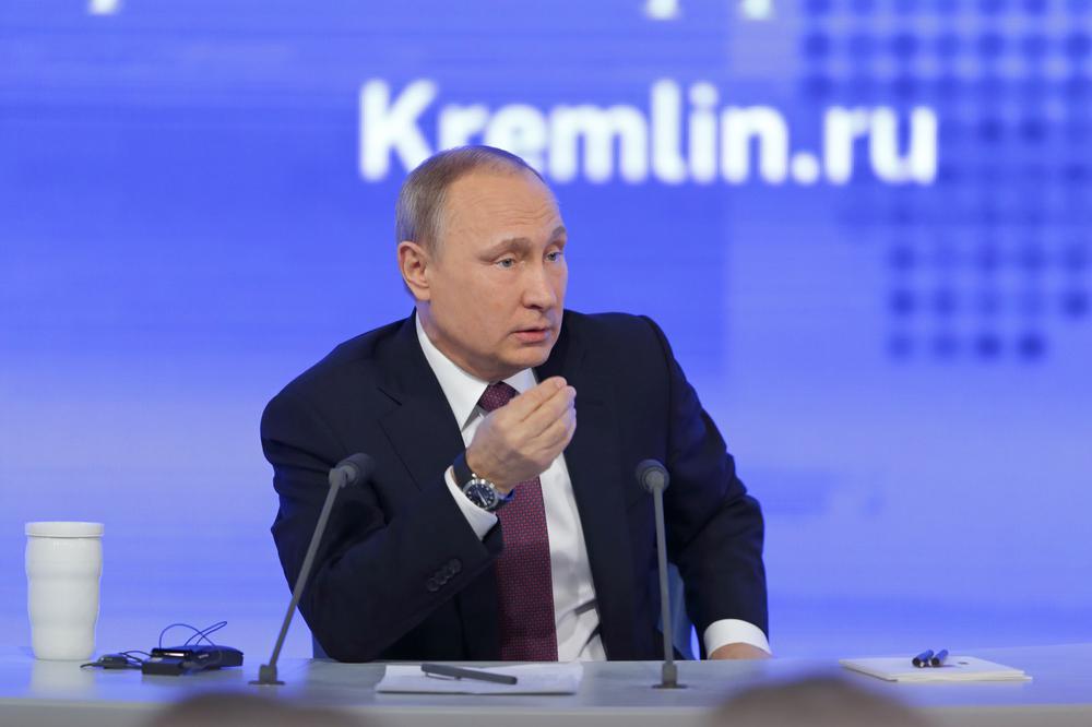 Vladimir Putin sitzt vor einem blauen Hintergrund an einem Tisch mit Mikrofon drauf.