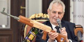 """Tschechiens Präsident Miloš Zeman sitzt mit einem Mikrophon an einem Tisch und hält ein Maschinengewehr in die Kamera, auf dem """"für Journalisten"""" steht."""