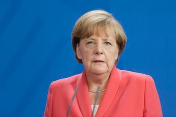 Angela Merkel am Rednerpult vor blauem Hintergrund.