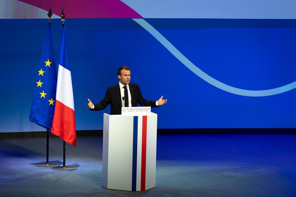 Emmanuel Macron steht auf einer großen Bühne hinter einem Rednerpult in Blau-Weiß-Rot vor einer Wand, an der geschwungen die gleichen Nationalfarben Frankreichs aufgemalt sind.