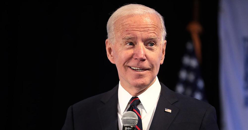 Joe Biden lächelt in die Kamera, ein Mundwinkel typisch etwas höher als der andere. Er trägt einen blauen Anzug.