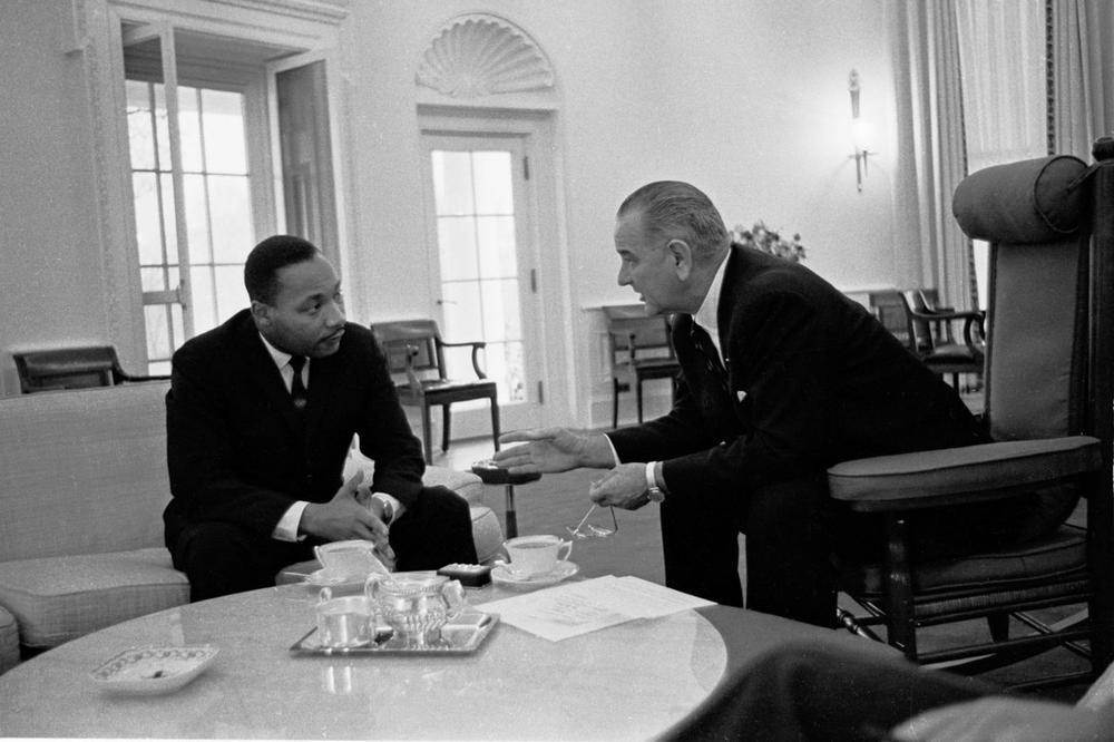 Martin Luther King sitzt auf einem Sofa, ihm gegenüber US-Präsident Lyndon B. Johnson, im Oval Office im Weißen Haus.