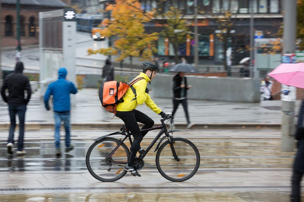Ein Fahrradbote rast bei Regen eine Straße entlang. Er trägt eine gelbe Regenjacke und auf dem Rücken eine rote Transportbox.