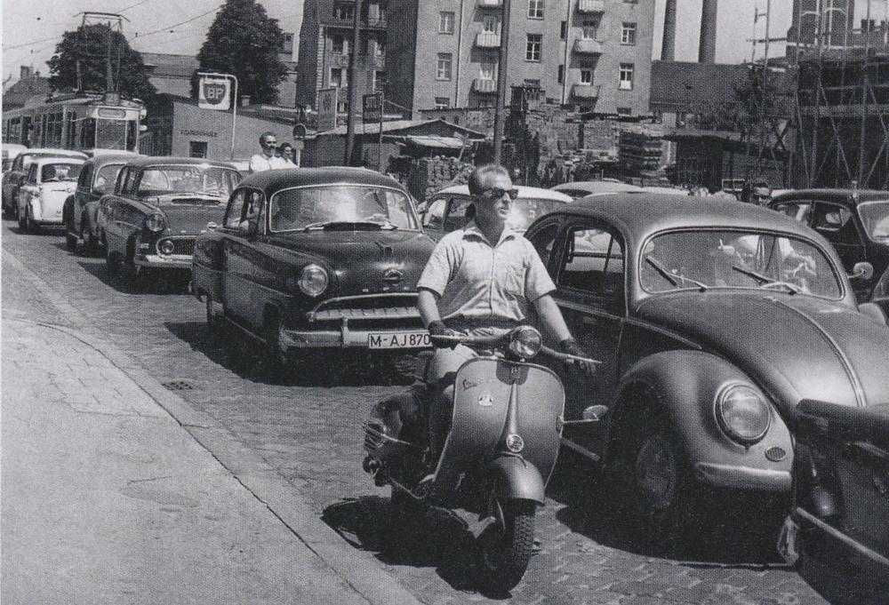 Auto hinter Auto, eine Straßenbahn im Hintergrund, ein Moped samt Fahrer im Vordergrund auf einem alten Foto aus den Fünfzigerjahren.