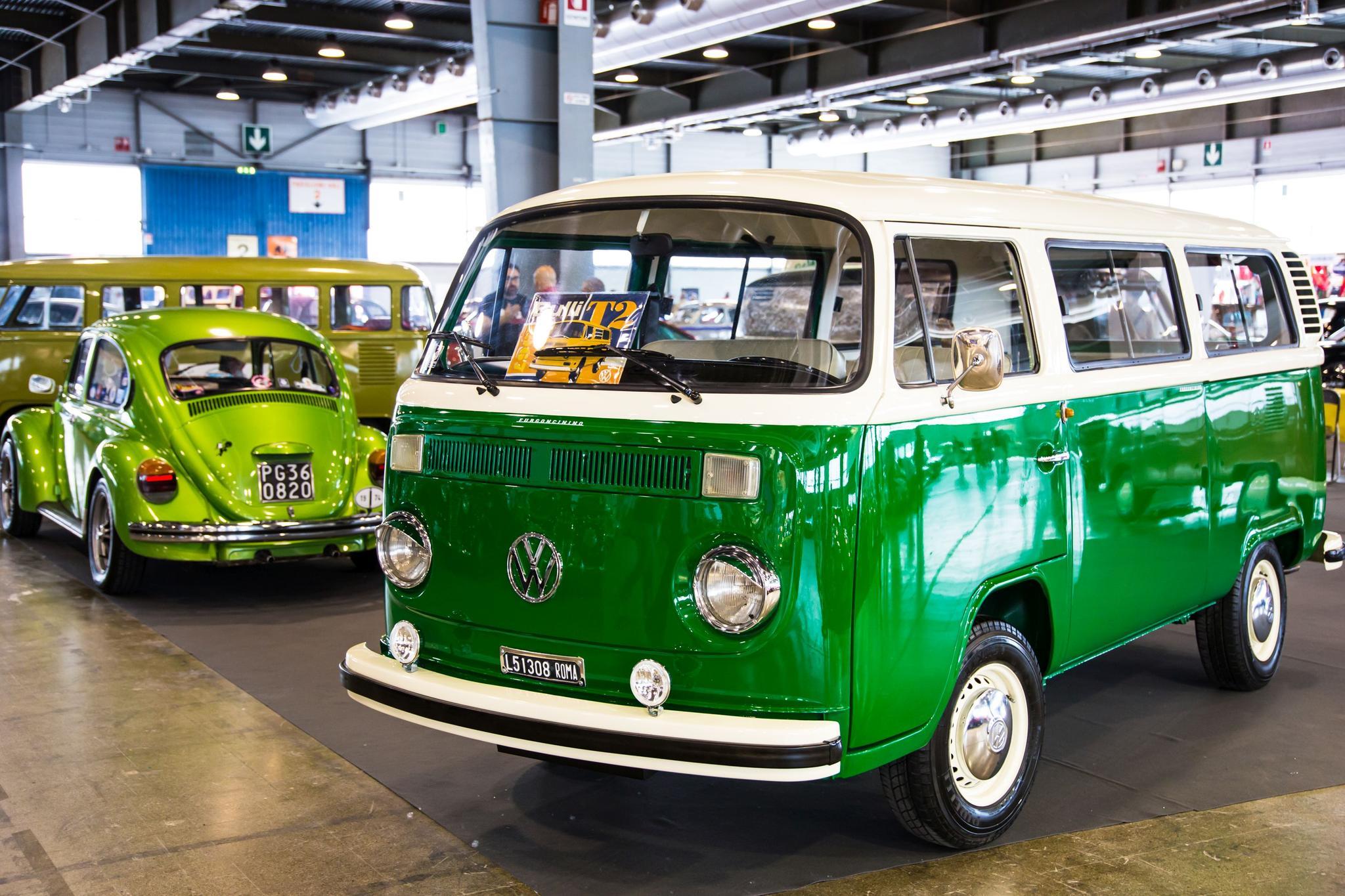 VW Käfer und ein VW Bus in Grün stehen in der Halle.