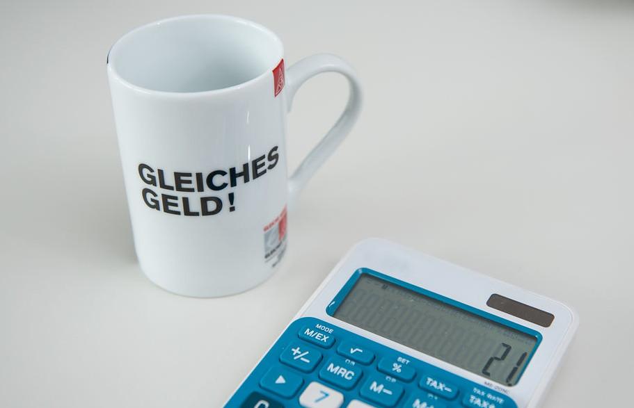 Eine weiße Tasse neben einem Taschenrechner. Auf der Tasse steht: Gleiches Geld!