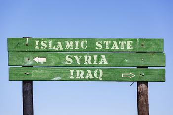 Grünes Schild aus Holz, auf dem steht von oben nach unten: Islamic Staat, Syria mit Pfleil nach links, Iraq mit Pfeil nach rechts.