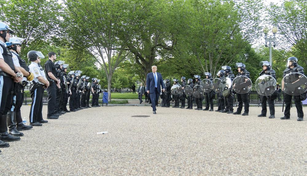 Donald Trump überquert eine Straße, rechts und links schirmen ihn bewaffnete Polizisten ab.