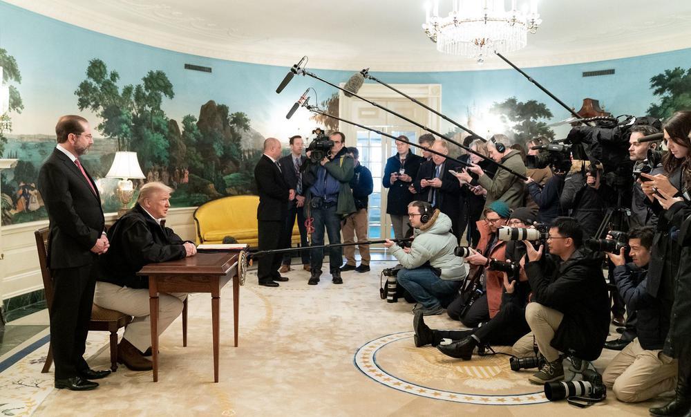 Donald Trump sitzt links an einem kleinen Tisch und unterzeichnet ein Dokument. Ihm gegenüber stehen etwa 20 Fotografen und ein paar Kameraleute und nehmen die Szene auf.