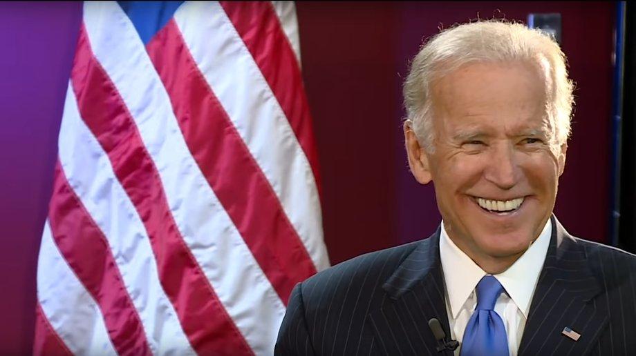 Joe Biden strahlt übers ganze Gesicht, neben ihm steht eine US-Flagge.