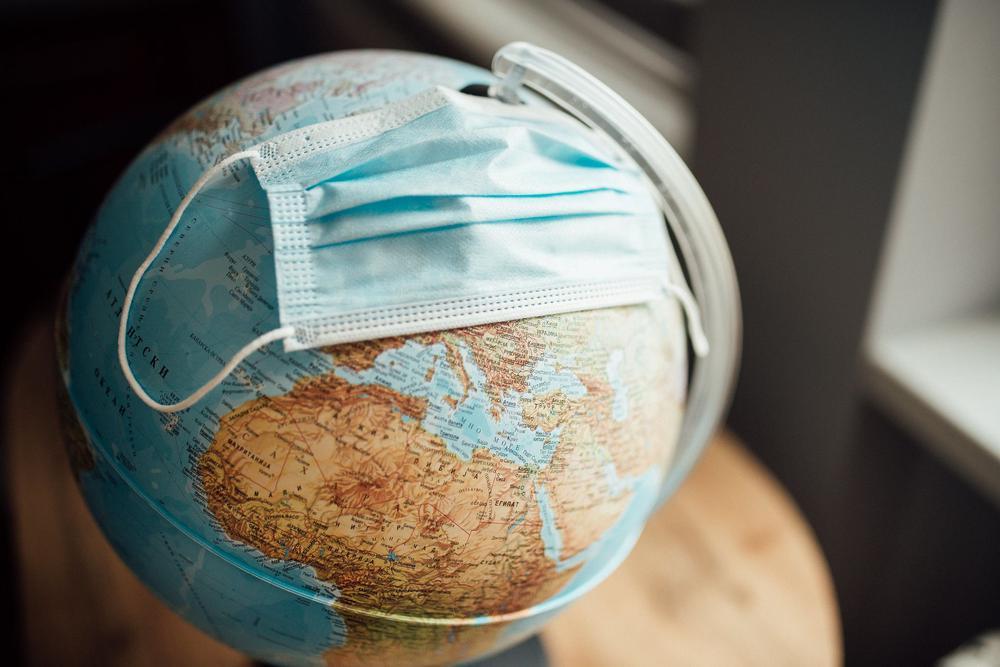Kleiner Globus auf dem eine Gesichtsmaske liegt.