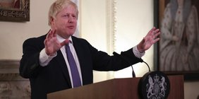 Boris Johnson steht mit ausgebreiteten Armen hinter einem Rednerpult.