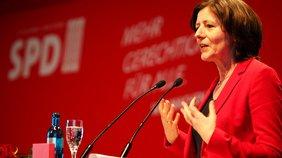 Malu Dreyer spricht hinter einem Rednerpult. Sie hat ein rotes Kostüm an vor einem roten Hintergrund.