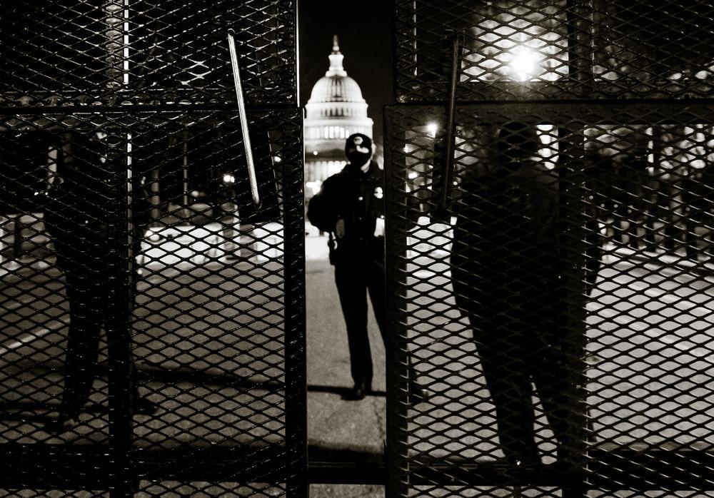 Schwarzbild mit einem bewachten Tor im Vordergrund, im Hintergrund ist das Kapitol in Washington zu erkennen.