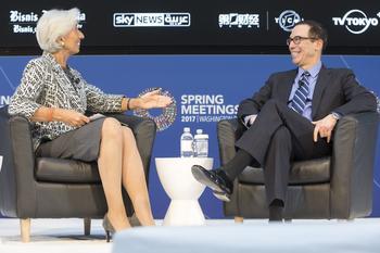 Christine Lagarde und Steven Mnuchin reden auf einem Podium miteinander.