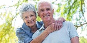 Ein Rentnerpaar blickt glücklich in die Kamera.