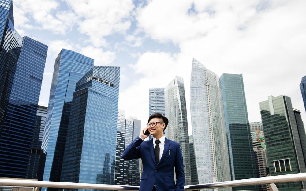 Ein asiatisch aussehender Mann in blauem Anzug telefoniert mit einem Handy vor einer glitzernden Kulisse von Hochhäusern.