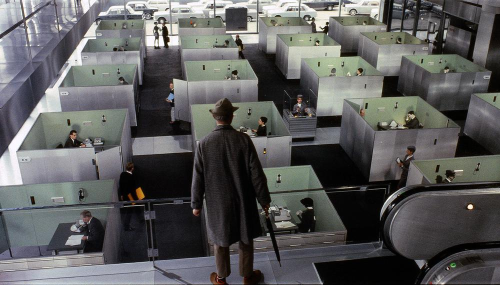 Bild aus Jacques Tatis Film Playtime, auf dem er von oben in ein Großraumbüro blickt. Alle Schreibtsiche stehen in kleinen Boxen, die in den großen Raum eingebaut sind.