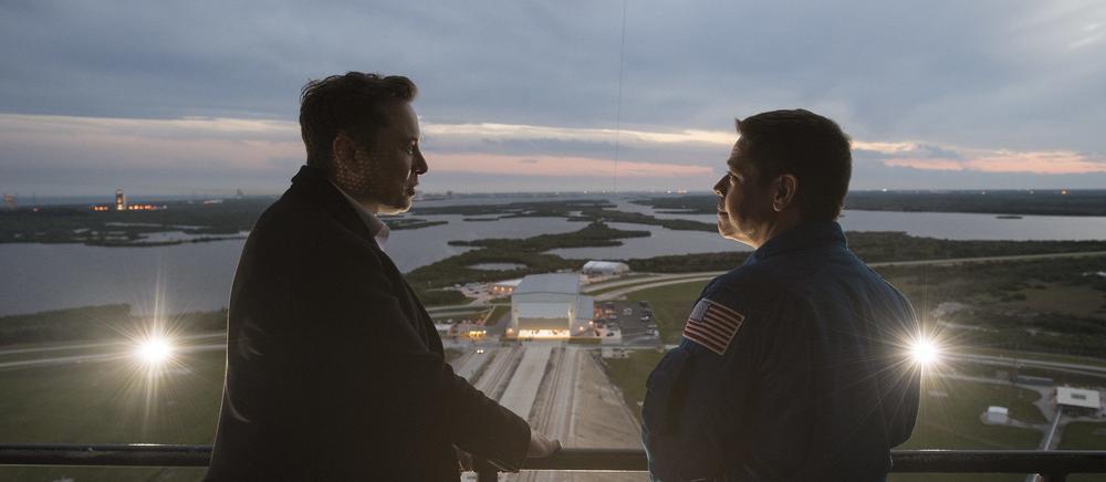 Zwei Männer stehen im Gegenlicht auf einem Balkon und schauen sich an. Im Hintergrund sind Seen zu sehen.