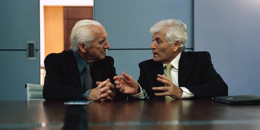 Zwei ältere Männer in Anzügen an einem Konferenztisch.