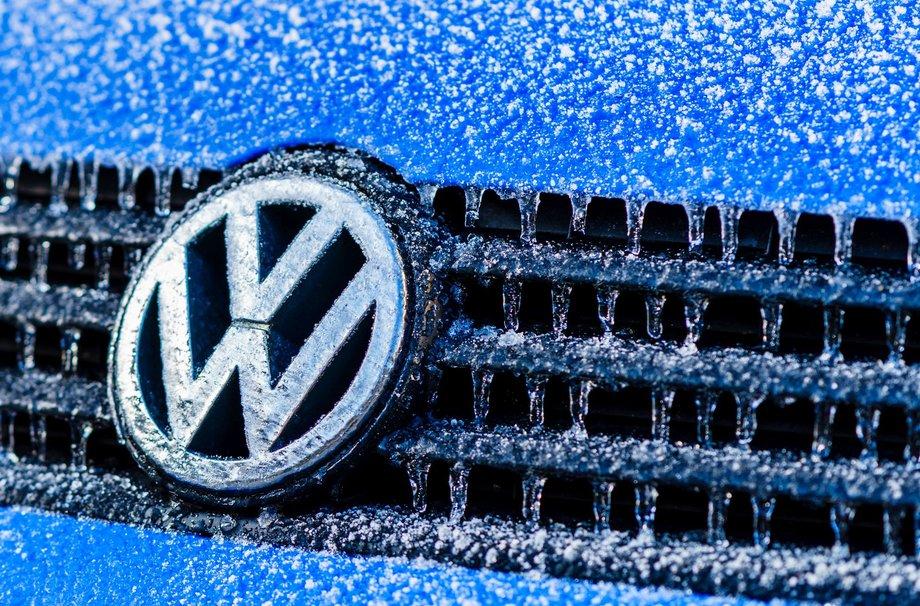 Ausschnitt von der Front eines Volkswagens mit Kühlergrillemblem von VW, der Wagen ist blau.